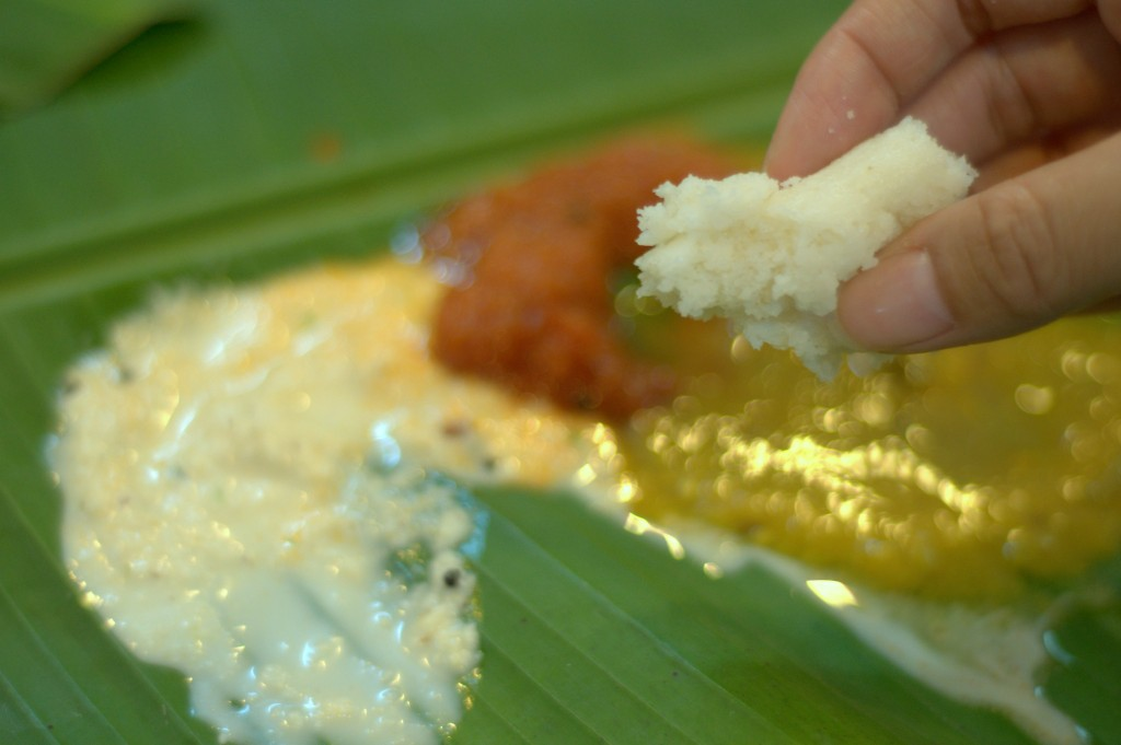 Enjoying my idli and Indian dipping sauces